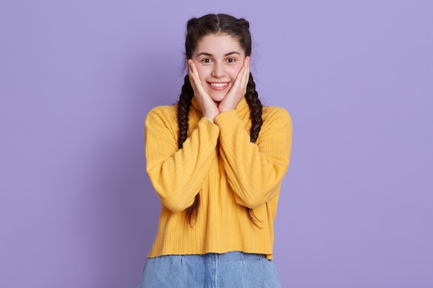 Foto van mooie opgewonden grappige kleine jonge vrouw met palmen op de wangen