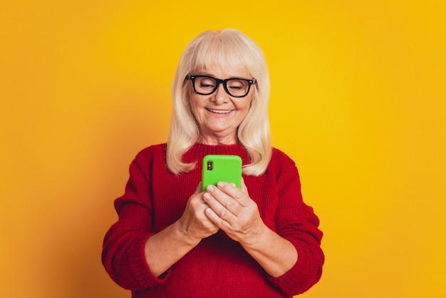 Foto van mooie oudere dame draagt een bril met schrijfapparaat geïsoleerd gele kleur achtergrond
