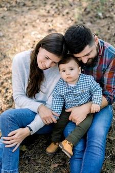 Foto van mooie ouders knuffelen kleine baby peuter zoon, in herfst park of bos, samen zitten en genieten van hun familie tijd, buiten spelen