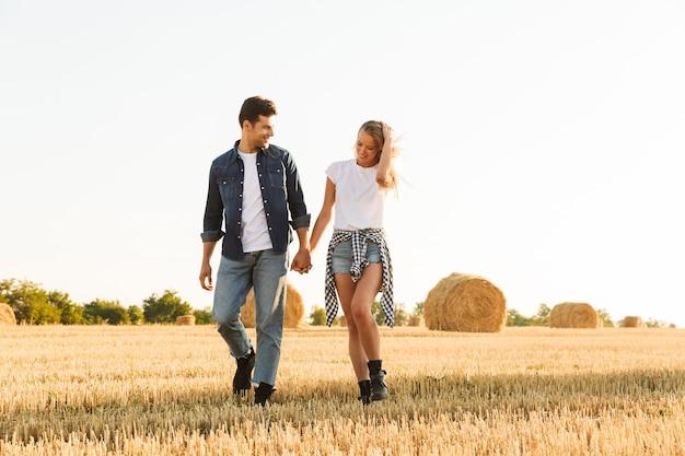 Foto van mooie paar man en vrouw lopen door gouden veld, met bos hooibergen tijdens zonnige dag