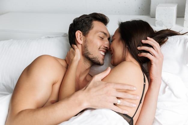 Foto van mooie paar man en vrouw samen zoenen, liggend in bed thuis of hotel appartement