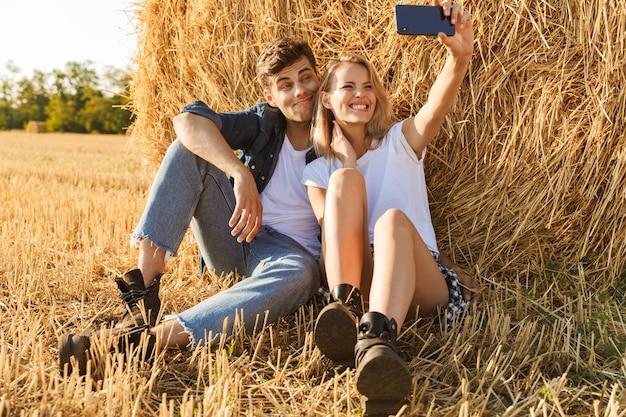 Foto van mooie paar man en vrouw selfie te nemen zittend onder grote hooiberg in gouden veld, tijdens zonnige dag