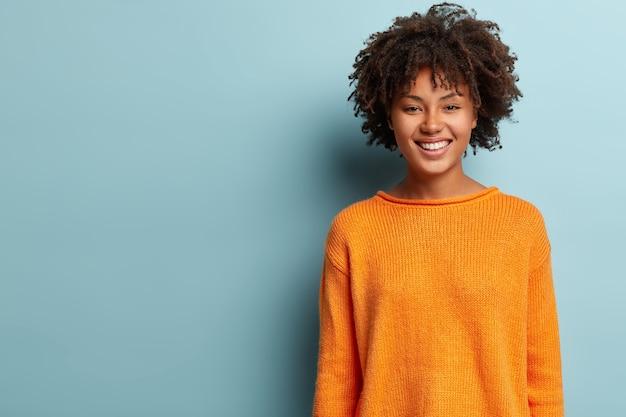 Foto van mooie positieve afro-amerikaanse vrouw met krullend haar, draagt een oranje trui, staat in hoogmoed over de blauwe muur met vrije ruimte voor uw promotionele inhoud. goed emoties concept