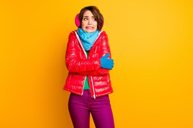 Foto van mooie reiziger dame koud ijzig weer reis nieuw land tanden schudden dragen stijlvolle casual korte rode overjas blauwe sjaal handschoenen oorbeschermers broek