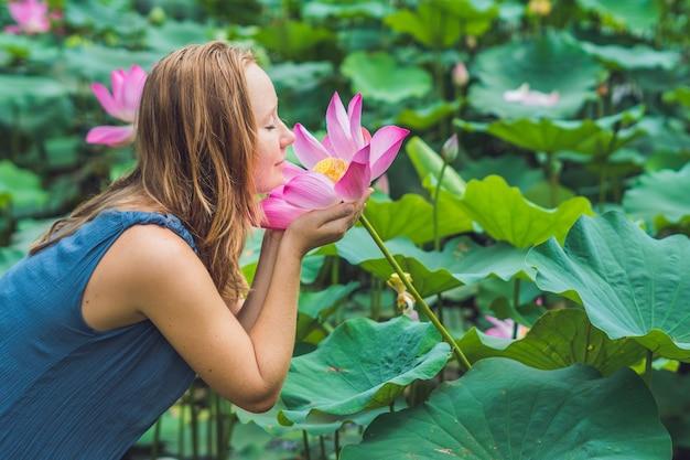 Foto van mooie roodharige vrouw met lotusbloem in hand