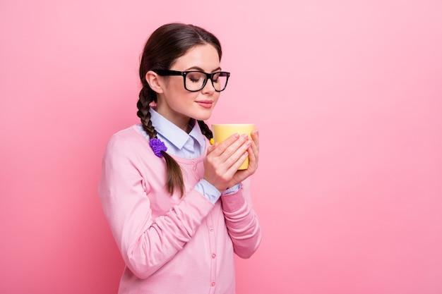 Foto van mooie student dame hand in hand warme verse drank beker ogen gesloten geniet van aangename geur kleine pauze huiswerk slijtage shirt pullover specificaties geïsoleerde pastel roze kleur achtergrond
