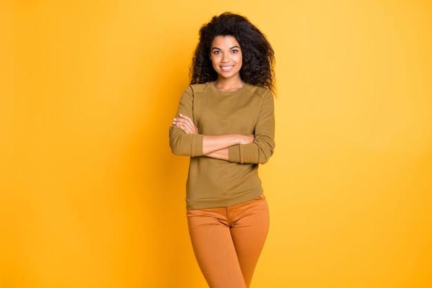Foto van mooie verbazingwekkende donkere huid zakelijke dame met armen gekruist positieve stemming dragen casual pullover broek geïsoleerde gele kleur achtergrond