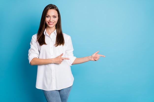 Foto van mooie verkoopmanager dame directe vingers kant lege ruimte draag wit overhemd jeans geïsoleerde blauwe kleur achtergrond