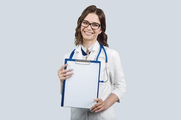 Foto van mooie vrolijke doc dame glimlach patiënten directe vinger lege ruimte verzekering aanbod klembord dragen witte laboratoriumjas