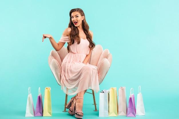 Foto van mooie vrouw 20s in jurk zittend op roze fauteuil na het winkelen met veel kleurrijke tassen, geïsoleerd over blauwe muur