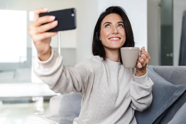 Foto van mooie vrouw 30s selfie op mobiele telefoon, zittend op de bank in lichte appartement
