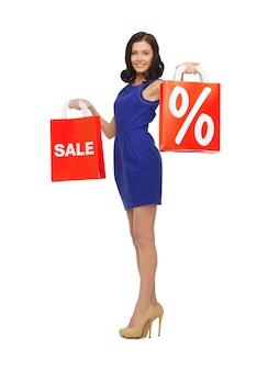 Foto van mooie vrouw in blauwe jurk met boodschappentas