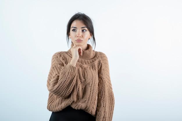 Foto van mooie vrouw in gebreide trui staande op witte achtergrond.