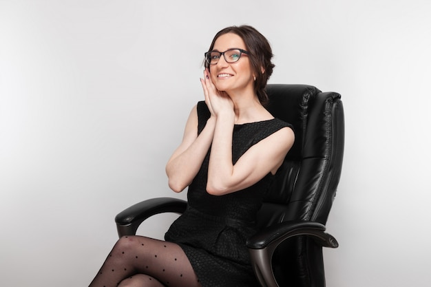 Foto van mooie vrouw in zwarte jurk zittend in de fauteuil