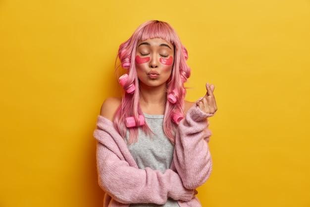 Foto van mooie vrouw maakt koreaans liefdesymbool met vingers, houdt de lippen rond en wacht op een kus, past schoonheidspatches en krulspelden toe, maakt kapsel