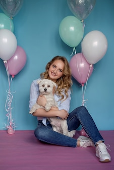 Foto van mooie vrouw met hond en vele kleurrijke ballons