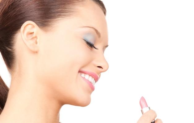Foto van mooie vrouw met lippenstift over wit