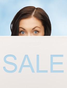 Foto van mooie vrouw met verkoopaanplakbord
