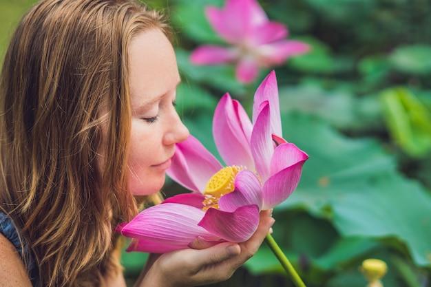 Foto van mooie vrouw roodharige met lotusbloem in hand.