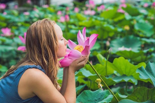 Foto van mooie vrouw roodharige met lotusbloem in hand