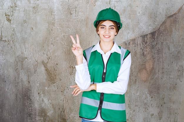 Foto van mooie vrouwelijke architect in groene helm die overwinningsteken toont