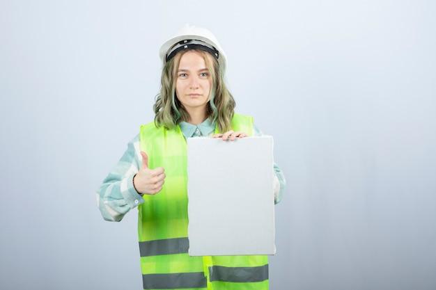 Foto van mooie vrouwelijke ingenieur die leeg canvas houdt en duimen opgeeft. hoge kwaliteit foto