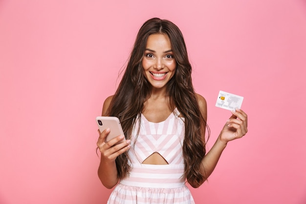 Foto van mooie vrouwen20s die kleding dragen die mobiele telefoon en creditcard houdt, die over roze muur wordt geïsoleerd