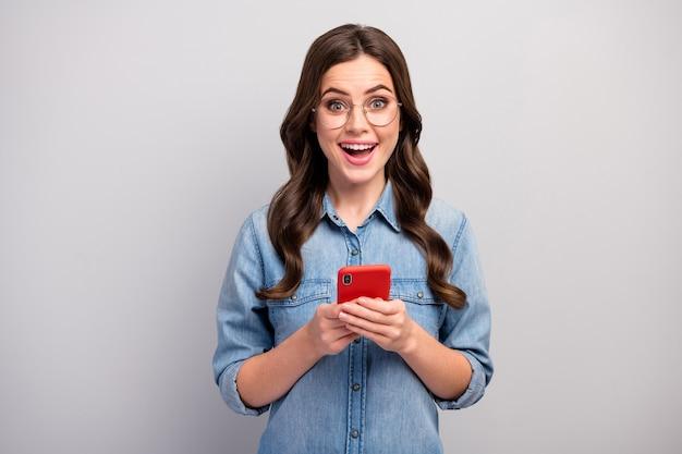 Foto van mooie zakelijke dame browsen telefoon check volgers abonnees verslaafde gebruiker open mond slijtage specs casual jeans denim overhemd geïsoleerde grijze kleur