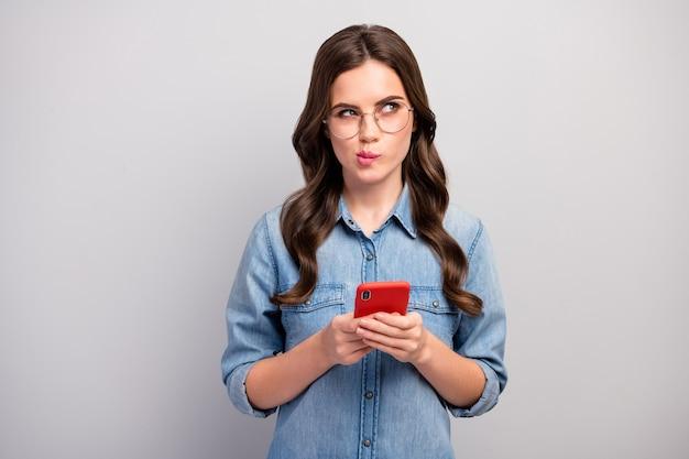 Foto van mooie zakelijke dame browsen telefoon diep denken lege ruimte schrijven creatieve jeugd thema post slijtage specs casual jeans denim overhemd geïsoleerde grijze kleur