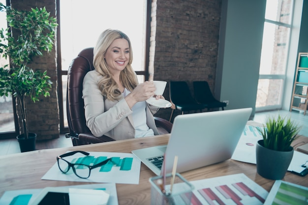 Foto van mooie zakelijke dame op zoek laptop scherm met koffiekopje