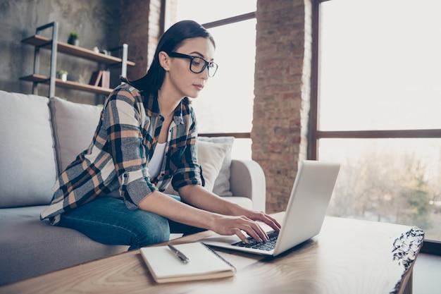Foto van mooie zakelijke dame sms-notebook collega's thuis werken voorbereid pen en planner om opstartdetails op te merken dragen casual kleding zitten sofa binnenshuis