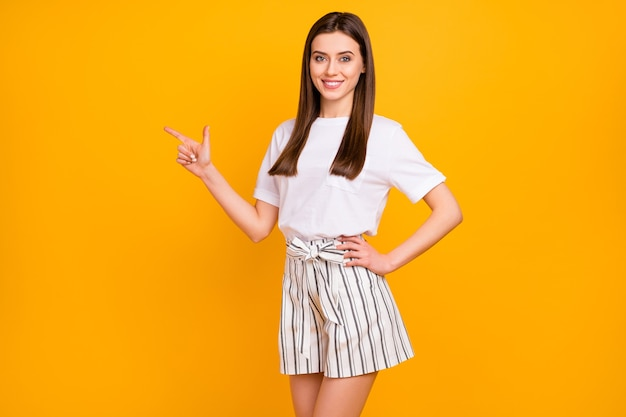 Foto van mooie zakelijke dame staande zelfverzekerd wijzend vinger kant lege ruimte dragen casual wit t-shirt gestreepte zomer mini korte broek geïsoleerde levendige gele kleur muur