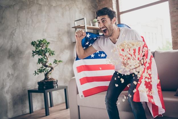 Foto van multi-etnisch gekke arabische kerel zittend bank houden popcorn emmer vuisten verhogen ter ondersteuning van vs voetbalteam match amerikaanse vlag op schouders jas platte kamer binnenshuis