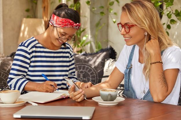 Foto van multi-etnische collega's bespreken ideeën voor een nieuw zakelijk project, hebben vrolijke uitdrukkingen in cafetaria met koffie. blonde vrouw luister audiotrack in oortelefoons, aziatisch meisje schrijft in dagboek