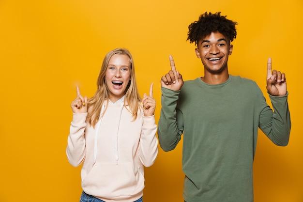 Foto van multi-etnische vrienden man en vrouw 16-18 met tandheelkundige beugels lachen en wijzende vingers naar boven op copyspace, geïsoleerd op gele achtergrond