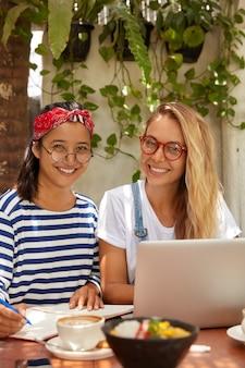 Foto van multi-etnische vrouwen laten onderzoek samenwerken: blonde vrouw in bril zoekt informatie op internet terwijl haar metgezel in notitieblok schrijft