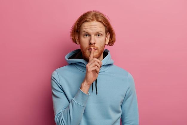 Foto van mysterieuze ernstig uitziende man met rood haar en baard maakt stilte gebaar, vraagt zijn geheime informatie niet te vertellen, drukt wijsvinger tegen de lippen, draagt blauwe hoodie ziet er direct uit