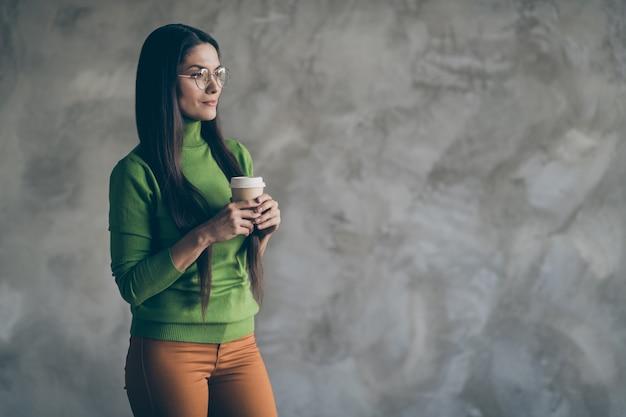 Foto van nadenkend doordachte geïnteresseerde vrouw met kopje warme drank in ornage broek broek op zoek naar lege ruimte geïsoleerde grijze kleur muur betonnen achtergrond