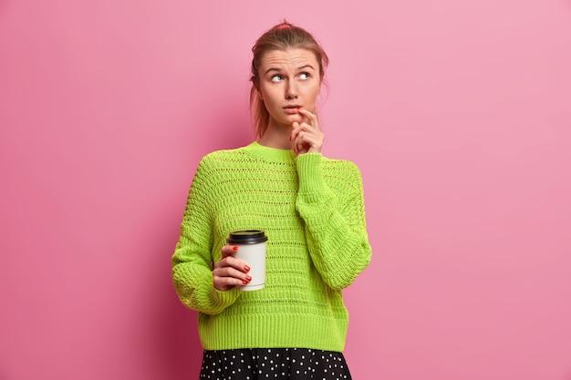 Foto van nadenkend duizendjarig meisje dat ergens opzij geconcentreerd is, houdt koffie vast om mee te nemen, neemt een pauze van het werk