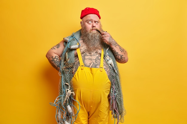 Foto van nadenkende mollige zeeman poseert met visnet rookt pijp trekt wenkbrauwen op met peinzende uitdrukking gekleed in overall getatoeëerd lichaam