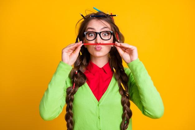 Foto van nerd meisje rommelig kapsel zet potlood neus lippen geïsoleerde gele kleur achtergrond