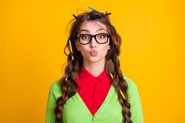 Foto van nerd tienermeisje met potloodkapsel stuurt luchtkus geïsoleerd over gele kleurachtergrond