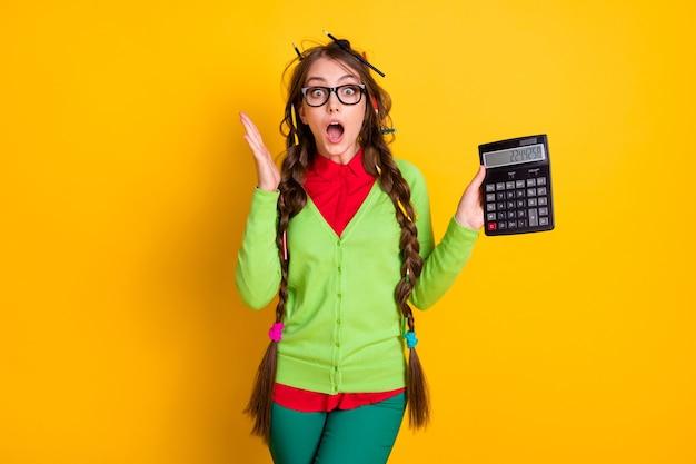 Foto van nerdmeisje met rommelig kapsel, rekenmachine, verbaasde geïsoleerde felle kleurachtergrond