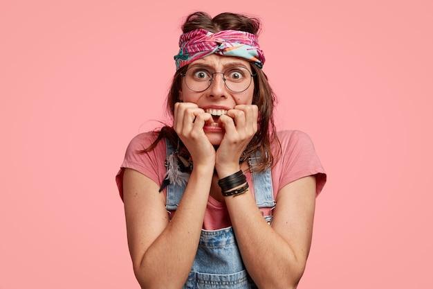 Foto van nerveuze angstige hippievrouw bijt vingernagels, draagt hoofdband