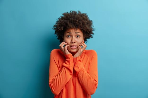 Foto van nerveuze bange vrouw grijpt gezicht en kijkt met bezorgde uitdrukking, ziet fobie, schrik van spreken, draagt oranje trui, geïsoleerd op blauwe muur. menselijke reactie concept