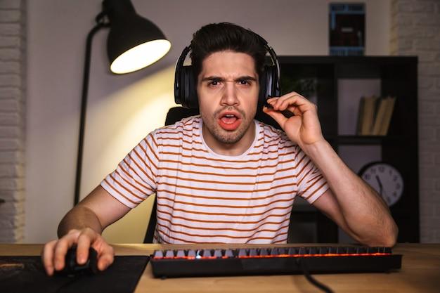 Foto van nerveuze man 20s spelen van videogames op computer in kamer, hoofdtelefoon dragen en kleurrijke toetsenbord met achtergrondverlichting gebruiken