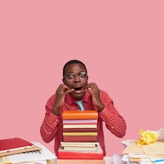 Foto van nerveuze zwarte man houdt handen in de buurt van de mond, staart met ogen vol angst, heeft stapel schoolboeken op bureau, papieren, schrikt van beantwoorden op examen