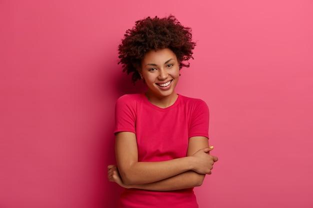 Foto van onbezorgde vrouw met natuurlijk krullend haar, houdt handen gekruist over lichaam, lacht aangenaam, heeft een informeel gesprek, draagt een t-shirt, geniet van een goede dag, geïsoleerd over roze muur. blije gevoelens
