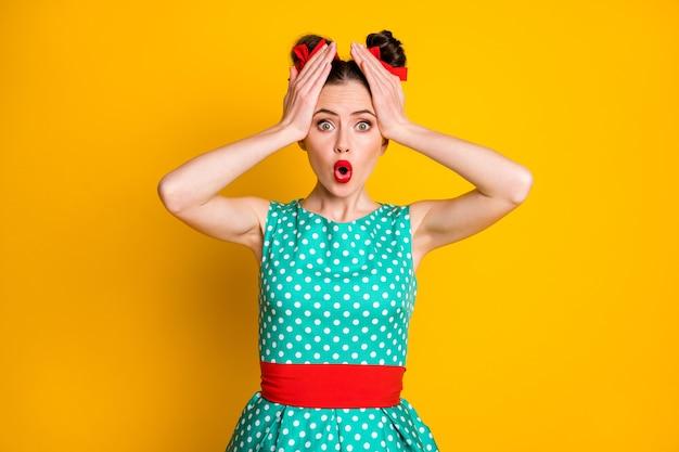 Foto van onder de indruk verbaasd verbijsterd meisje met hoofdhanden draagt groenblauwe outfit geïsoleerd over levendige kleurenachtergrond
