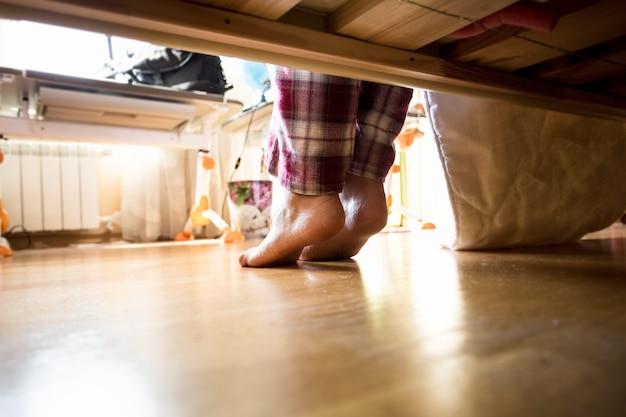 Foto van onder het bed op blote voeten vrouw in pyjama 's ochtends